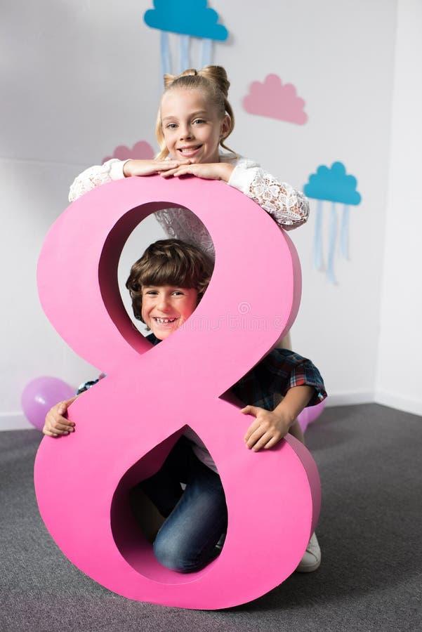 entzückende glückliche Kinder, die mit dekorativer rosa Nr. acht aufwerfen stockbild