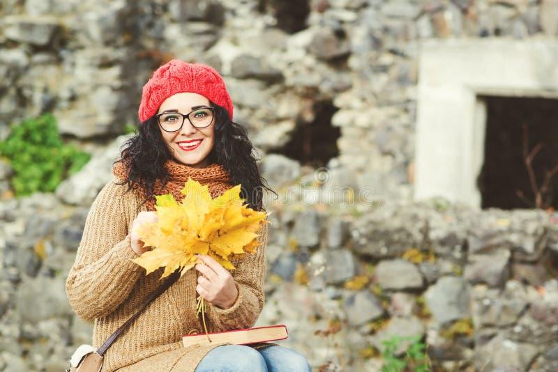 Entzückende junge Frau in der roten Strickmütze, die Blumenstrauß von Ahornblättern hält und schönen Herbst genießt stockbild