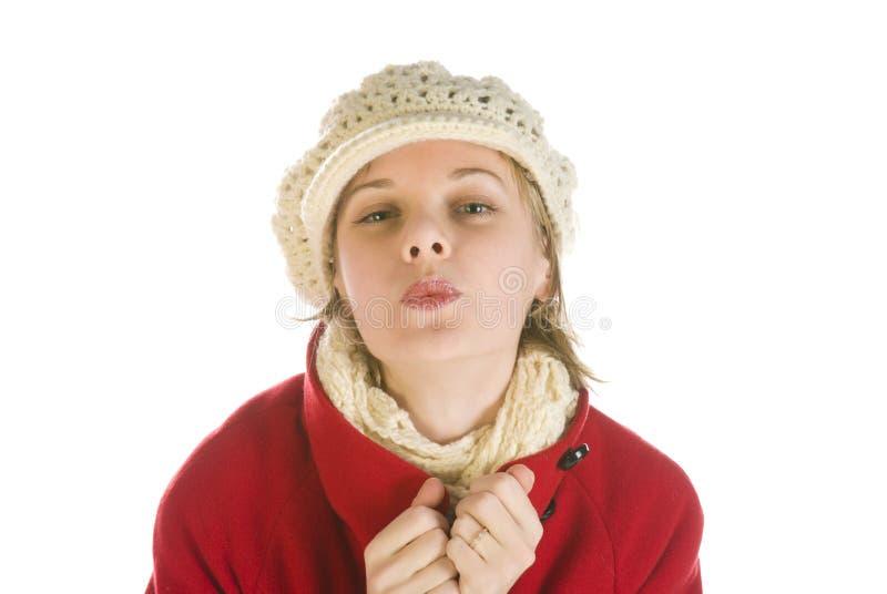 Entzückende junge Frau in einem Winterschutzkappenküssen stockfotos