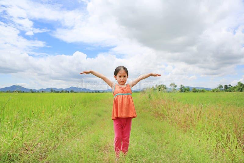 Entzückende kleine asiatische Kindermädchen-Ausdehnungsarme und entspannt an den jungen grünen Reisfeldern mit Gebirgs- und Wolke stockfotos
