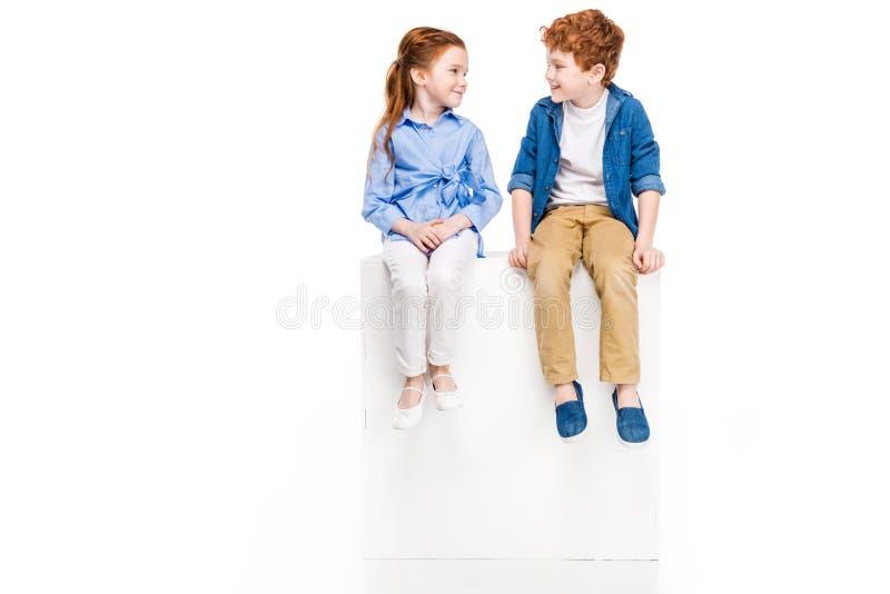 entzückende kleine auf weißem Würfel sitzende und lächelnde Kinder stockfoto