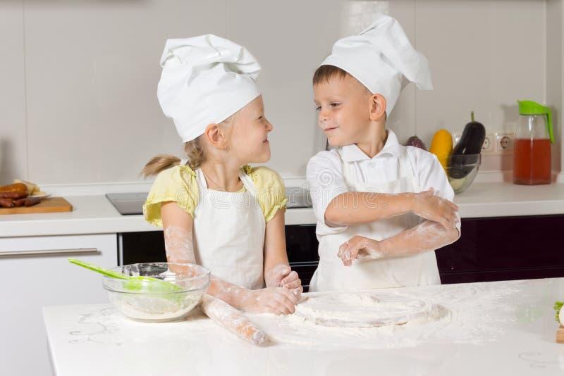 Entzückende kleine Chefs, die an der Küche spielen stockbild