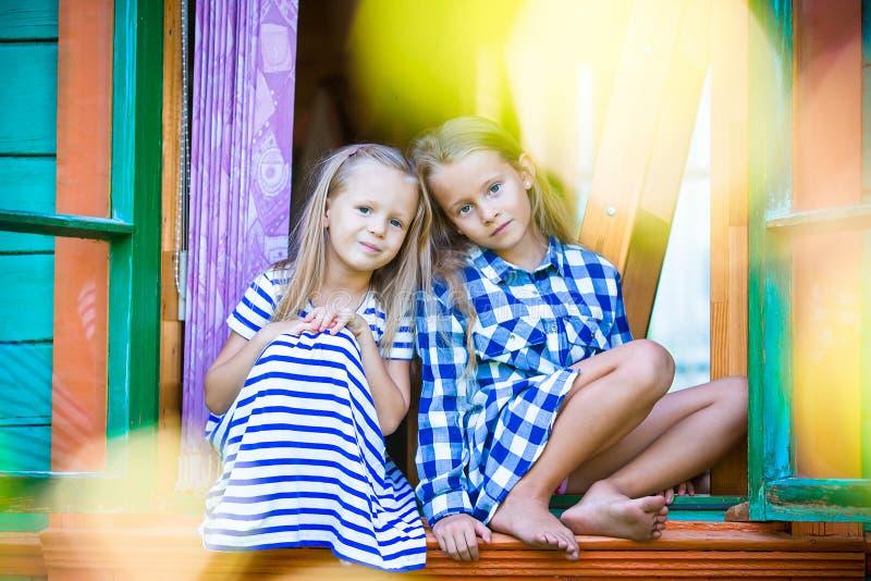 Entzückende kleine Mädchen im Fenster des ländlichen Hauses lizenzfreies stockfoto