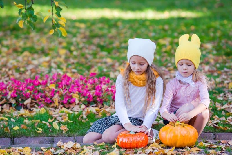 Entzückende kleine Mädchen mit Kürbisen draußen an lizenzfreies stockbild