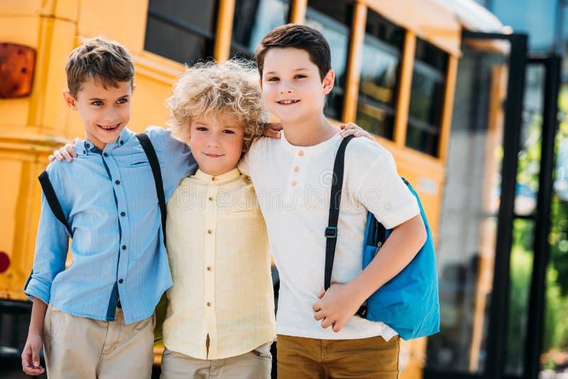 entzückende kleine Schüler, die vor Schulbus und dem Schauen umfassen stockbild