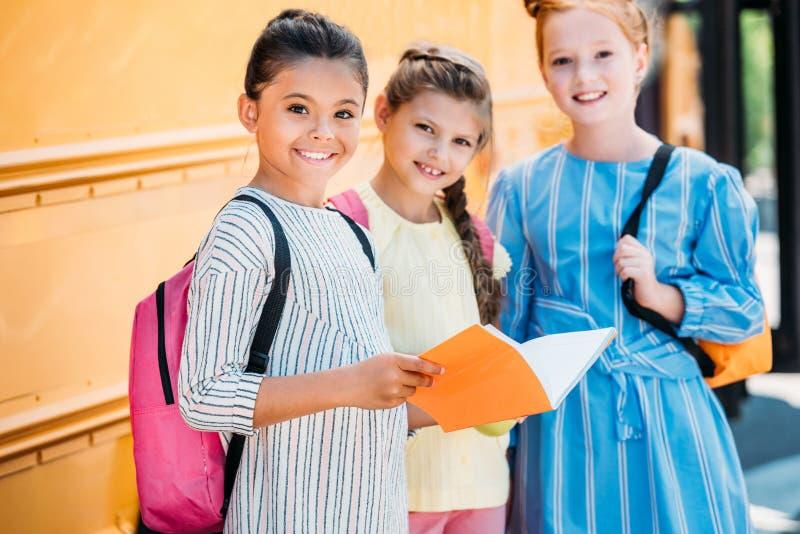 entzückende kleine Schulmädchen mit dem Notizbuch, das Kamera vor betrachtet lizenzfreie stockfotos
