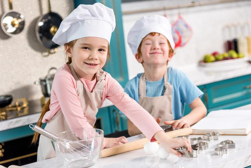 entzückende Kleinkinder in den Chefhüten und Schutzbleche, die an der Kamera beim zusammen kochen lächeln lizenzfreies stockbild