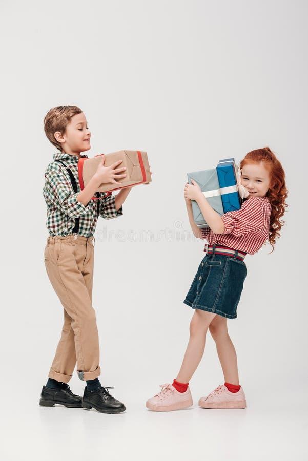entzückende Kleinkinder, die bunte Geschenkboxen halten stockbild