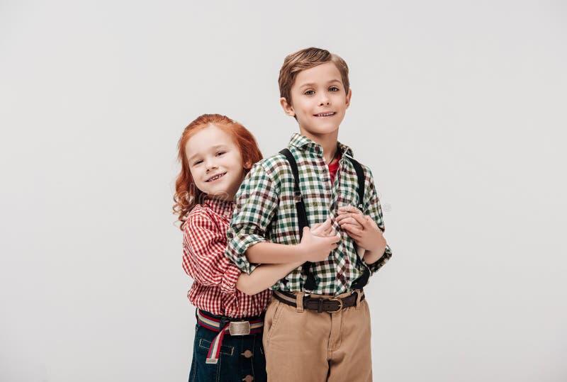 entzückende Kleinkinder, die an der Kamera umarmen und lächeln lizenzfreie stockbilder