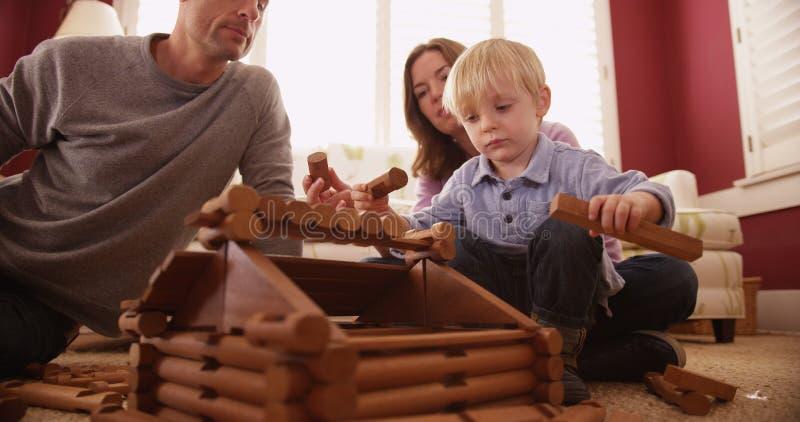 Entzückende Kleinkinder, die ein Holzhaus mit Familie bauen lizenzfreie stockfotos