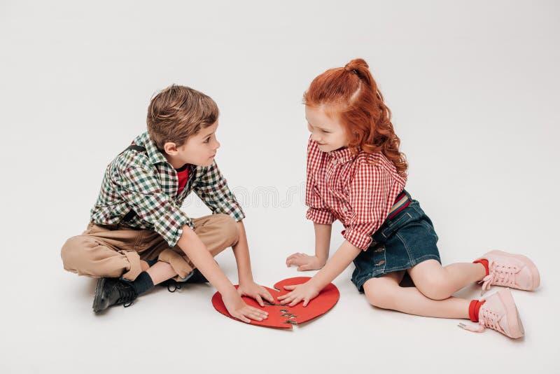 entzückende Kleinkinder, die Teile des Symbols des defekten Herzens zusammenfügen lizenzfreie stockfotos