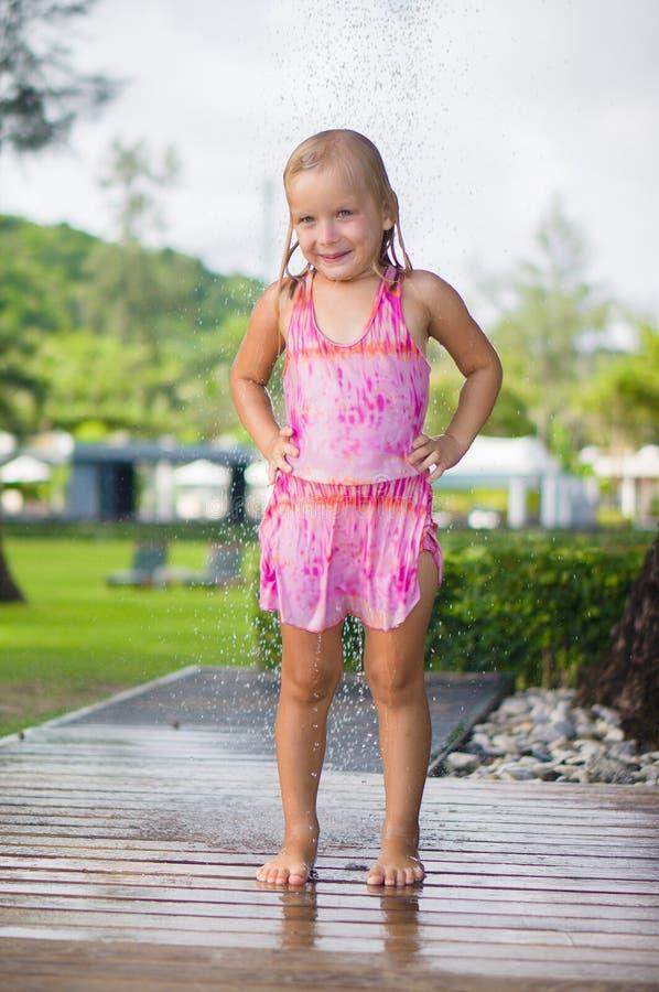 Entzückende Mädchennehmendusche unter Baum am tropischen Strandurlaubsort lizenzfreie stockfotografie