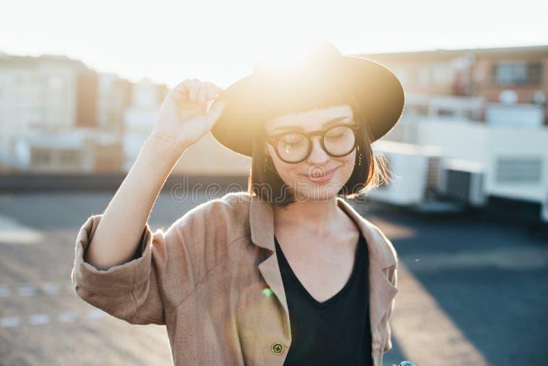 Entzückende nette Frau im Fedorahut bei Sonnenuntergang stockfoto