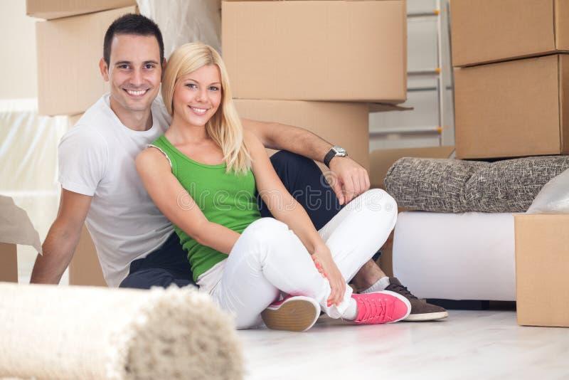 Entzückende Paare, die im neuen Haus sitzen lizenzfreie stockfotografie