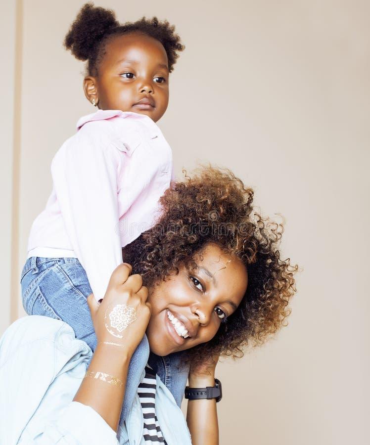 Entzückende süße junge afroe-amerikanisch Mutter mit netter kleiner Tochter, zu Hause hängend und haben den Spaß, der das Lächeln stockbild