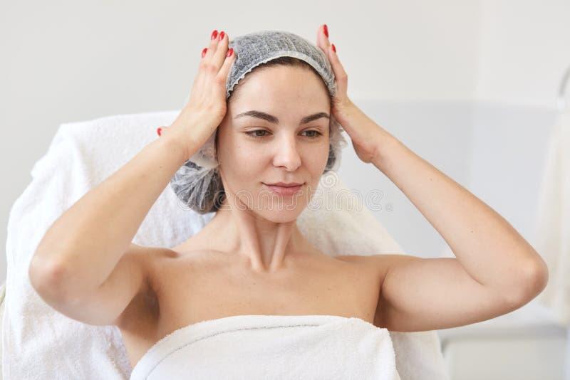 Entzückende süße junge Dame mit der roten Maniküre, die ihre Hände auf Kopf, tragende medizinische Kappe, sitzend im kosmetischen lizenzfreies stockbild