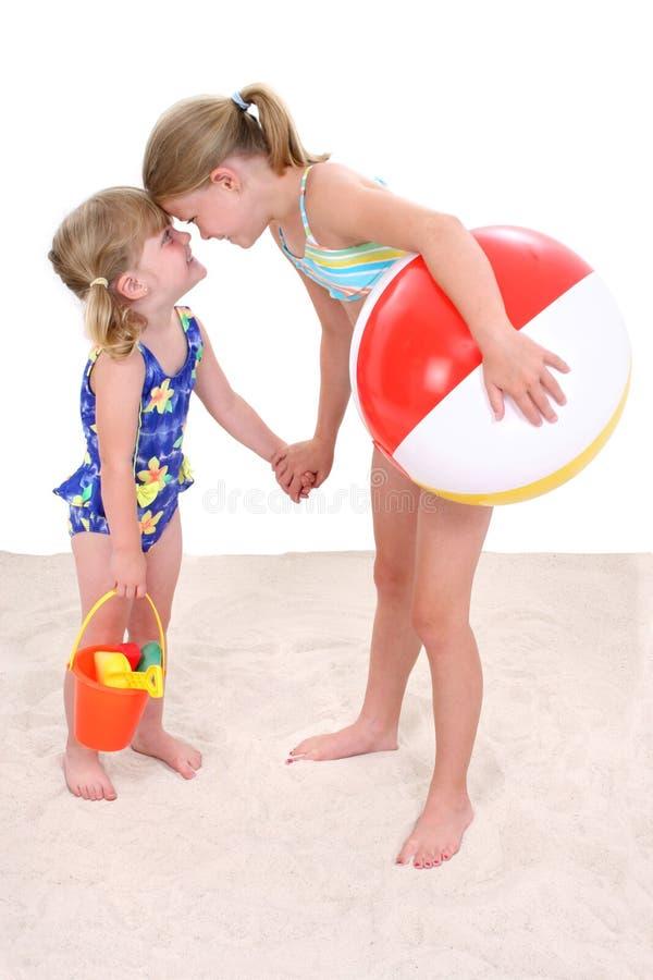 Entzückende Schwestern, die im Sand spielen lizenzfreie stockfotos