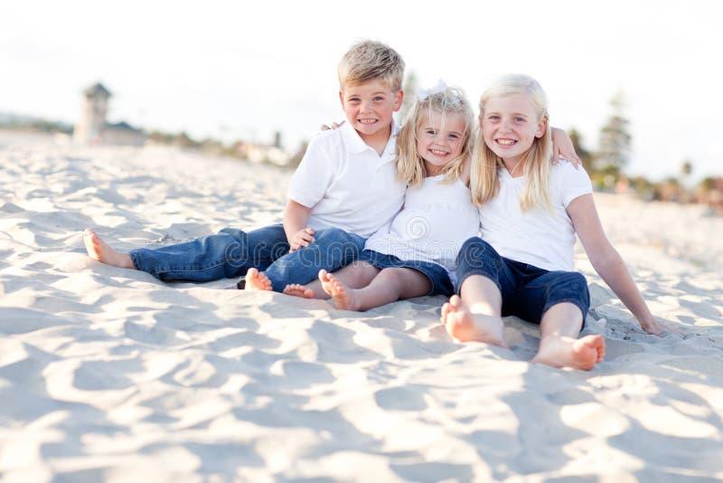 Entzückende Schwestern und Bruder Having Fun am Strand stockfotos