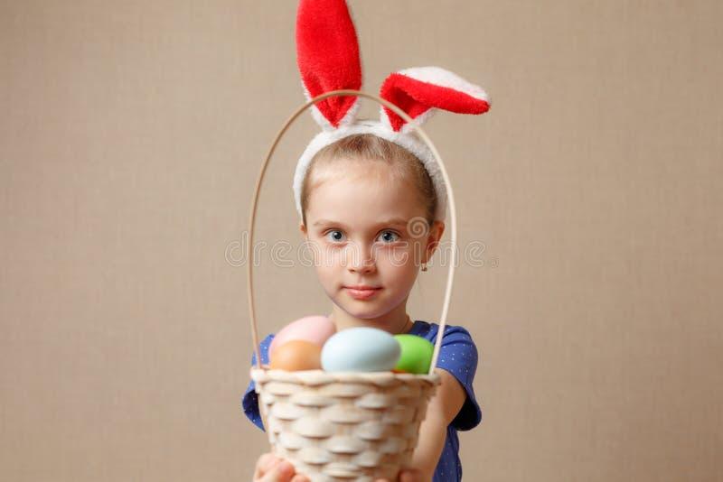 Entzückende tragende Häschenohren des kleinen Mädchens, die mit Ostereiern spielen stockfotografie