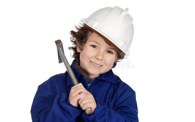 Entzückende zukünftige Arbeitskraft mit einem Hammer und einem Sturzhelm stockbild