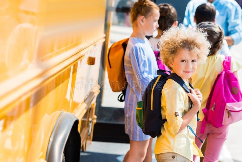 entzückender gelockter Schüler mit seiner Mitschüler-Stellung stockfoto