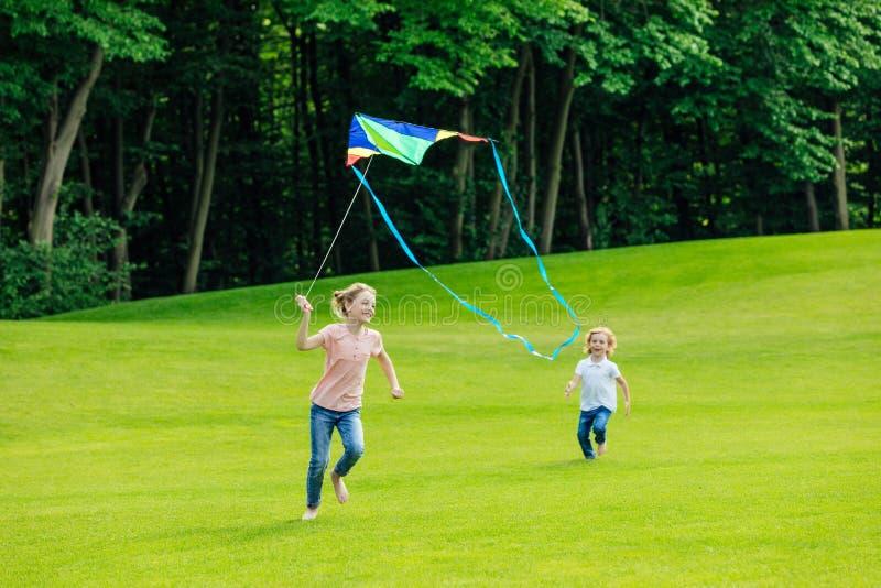entzückender glücklicher Bruder und Schwester, die mit Drachen auf grüner Wiese spielt stockbild