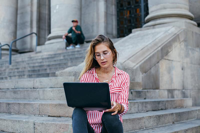 Entzückender hübscher Student sitzt auf Treppe mit Laptop lizenzfreies stockfoto