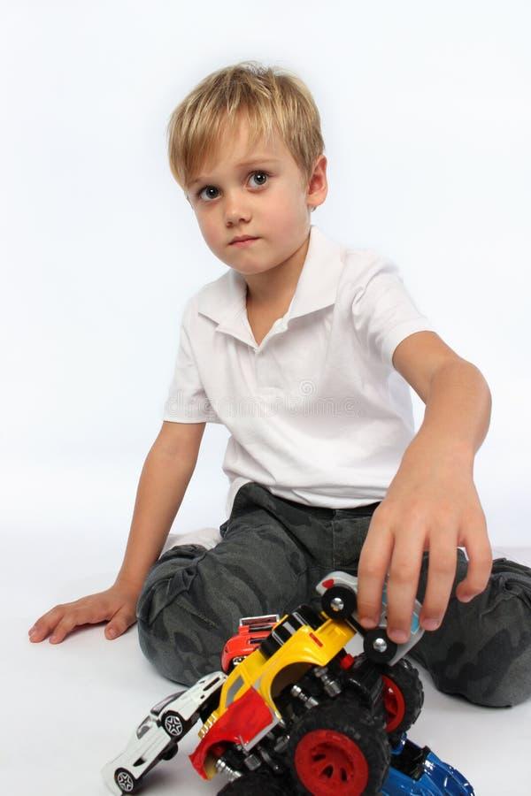 Entzückender Junge, der mit einem Stapel von Autospielwaren spielt lizenzfreies stockbild