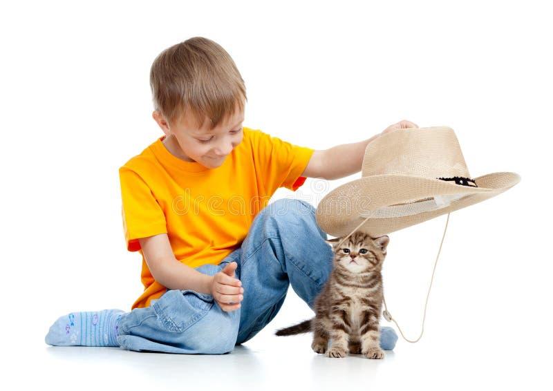 Entzückender Junge, der mit Kätzchen spielt stockfotografie