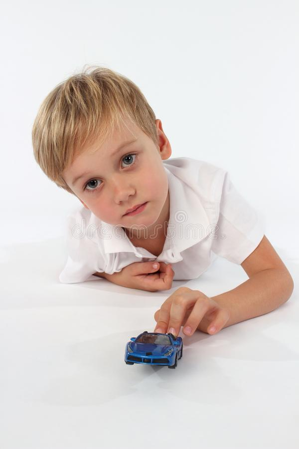 Entzückender Junge, der mit seinem Lieblingsautospielzeug spielt lizenzfreies stockbild
