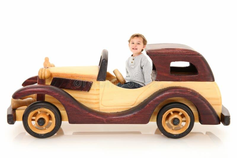 Entzückender Junge im hölzernen Auto stockfotos