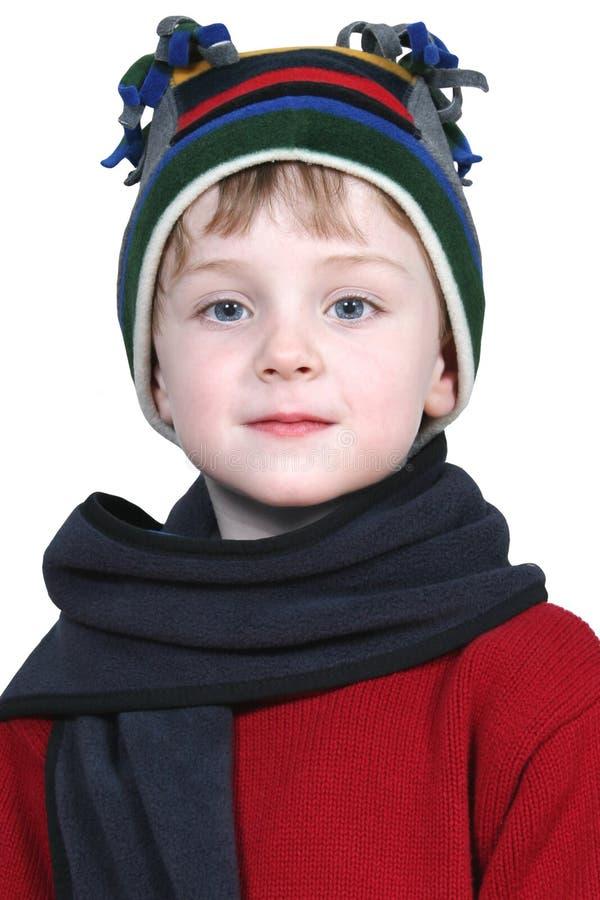 Entzückender Junge im Winter-Hut und in der roten Strickjacke stockbilder