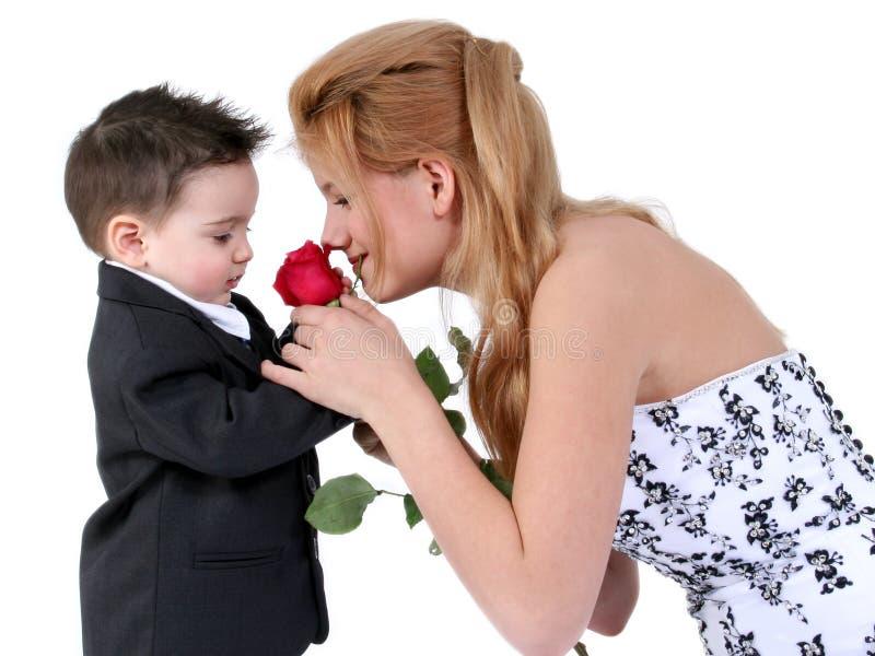 Entzückender Junge, schönes Mädchen, reizende Rose lizenzfreies stockfoto