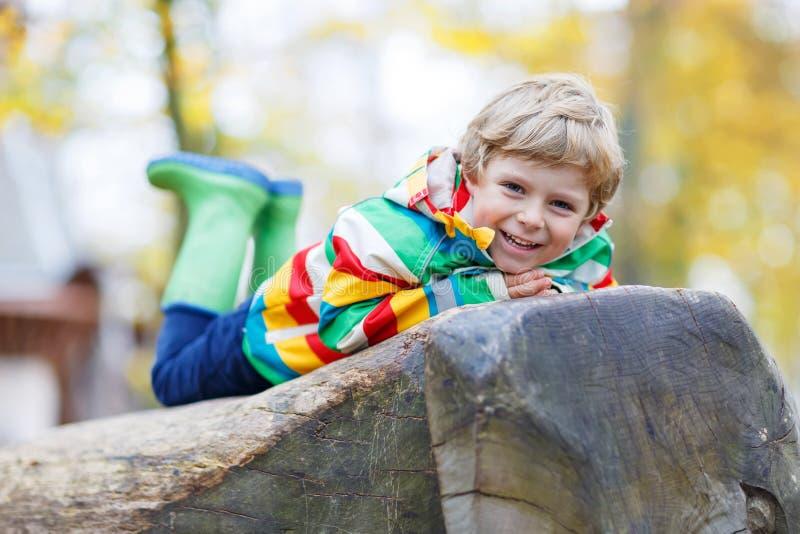 Entzückender Kinderjunge, der Spaß auf Herbstspielplatz hat stockbilder