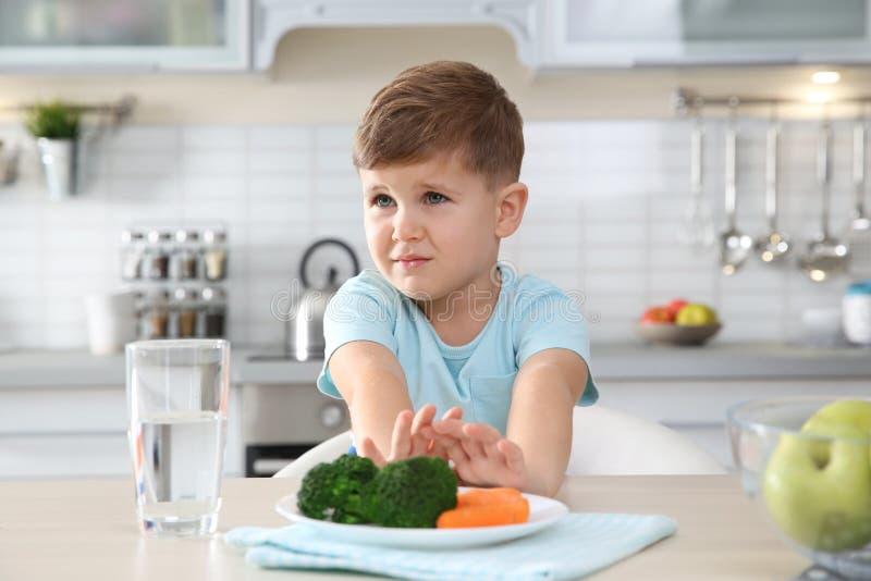 Entzückender kleiner Junge, der ablehnt, Gemüse bei Tisch zu essen lizenzfreies stockfoto