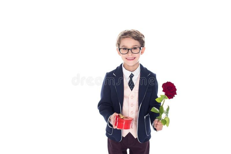 entzückender kleiner Junge in der Klage und die Brillen, die rosafarbene Blume und Herz halten, formten rote Geschenkbox stockfoto