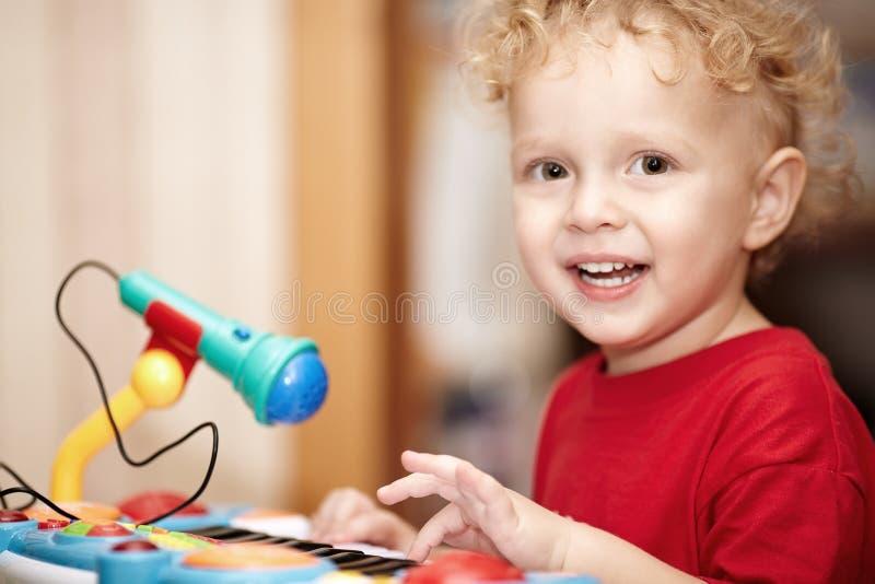Entzückender kleiner Junge, der mit einem Spielzeugmikrofon spielt stockbild