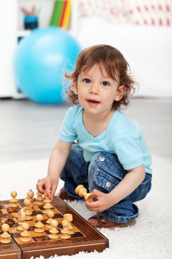 Entzückender kleiner Junge, der mit Schachstücken spielt lizenzfreies stockfoto