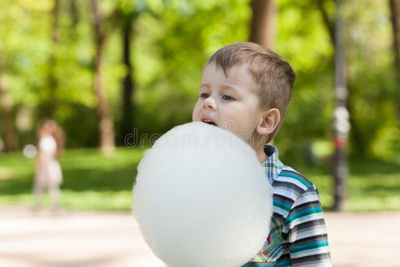 Entzückender kleiner Junge, der weiße süße Zuckerwatte isst stockbild