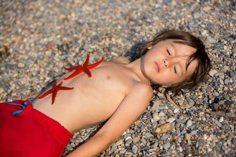 Entzückender kleiner Junge, liegend im Sand auf dem Strand, zwei Rot sta lizenzfreies stockfoto