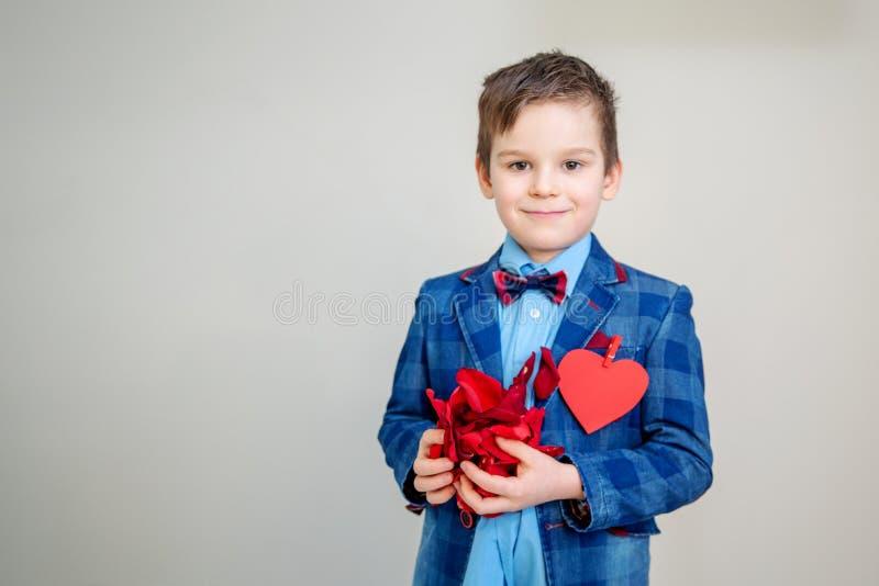 Entzückender kleiner Junge mit den roten rosafarbenen Blumenblättern stockfotos