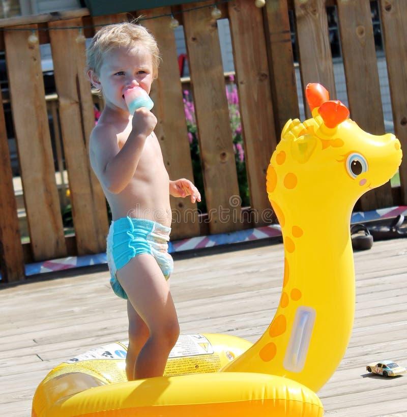 Entzückender Kleinkind-Junge, der ein Eis am Stiel durch das Pool isst stockfoto