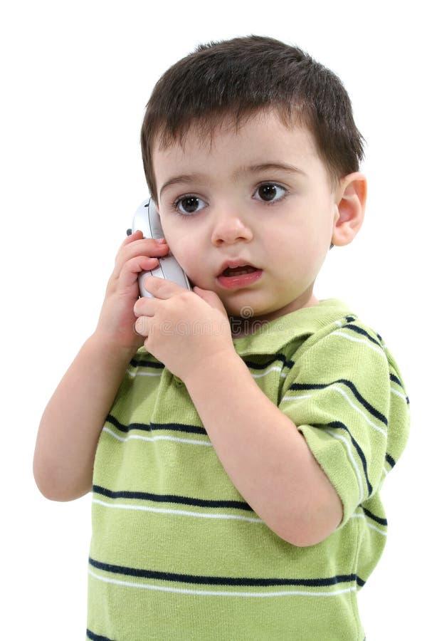 Entzückender Kleinkind-Junge, der an einem drahtlosen Telefon über Weiß spricht lizenzfreie stockbilder
