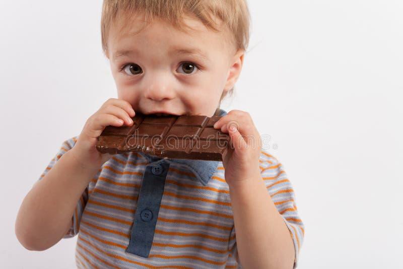 Entzückender Kleinkindjunge, der eine Platte der Schokolade isst lizenzfreie stockbilder