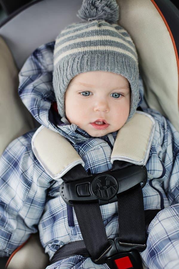Entzückender Kleinkindjunge, der im Autositz sitzt stockbild