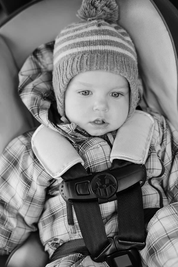 Entzückender Kleinkindjunge, der im Autositz sitzt stockfotografie