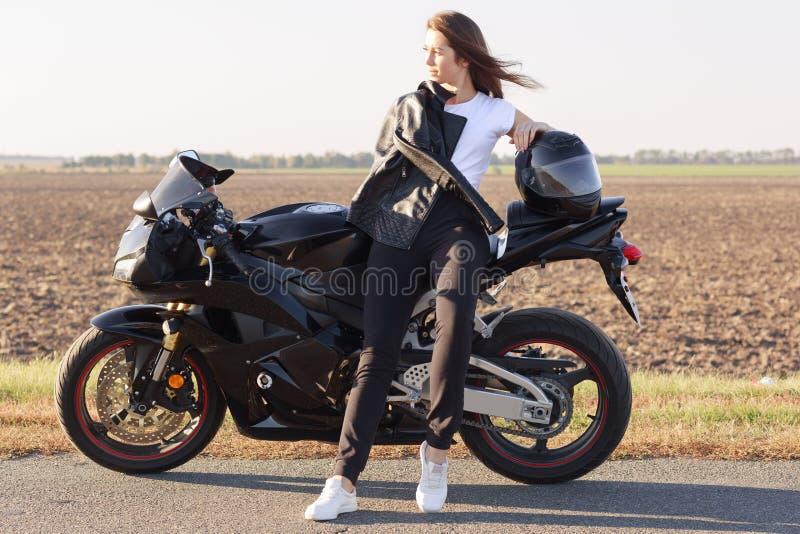 Entzückender magnetischer Radfahrer, der Reise auf ihrem Motorrad, Stellungsnahfeld, herrliche Ansichten genießend hat und beisei stockfotos