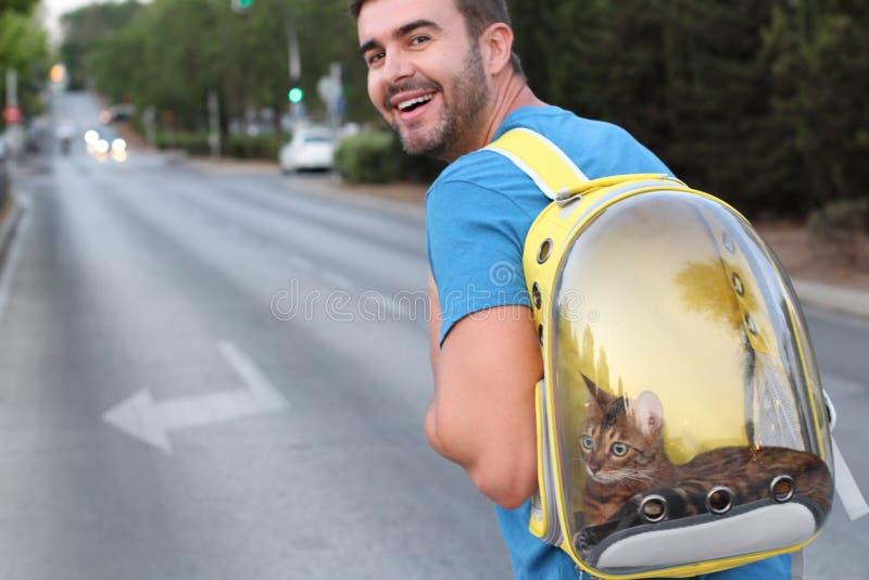 Entzückender Mann, der seine Katze im Blasenartrucksack trägt lizenzfreie stockbilder