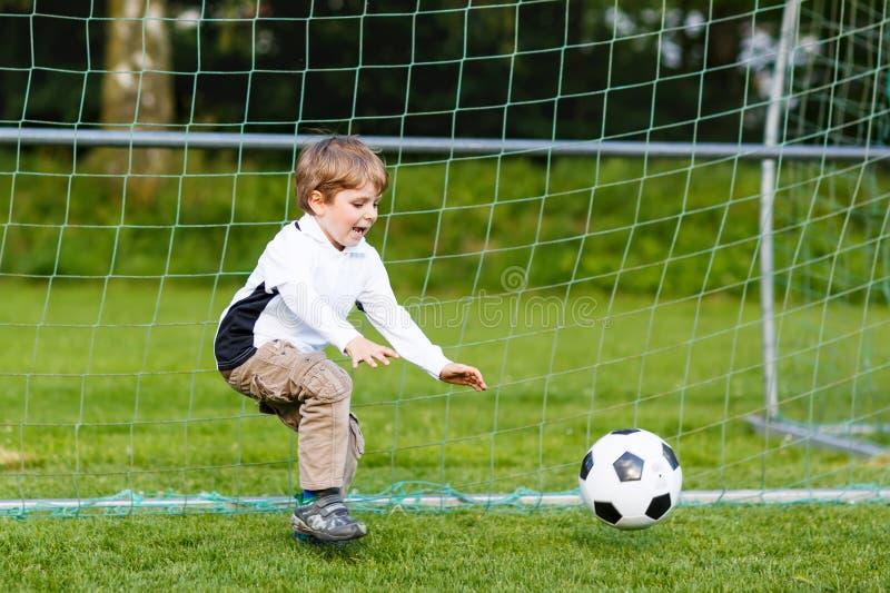 Entzückender netter Kleinkindjunge, der Fußball und Fußball auf Feld spielt stockfoto