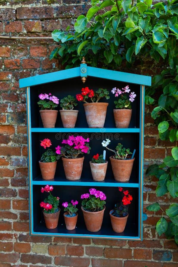 Entzückender Pflanzerkasten, der an einer Backsteinmauer mit hell farbigen Topfpflanzen hängt lizenzfreies stockfoto